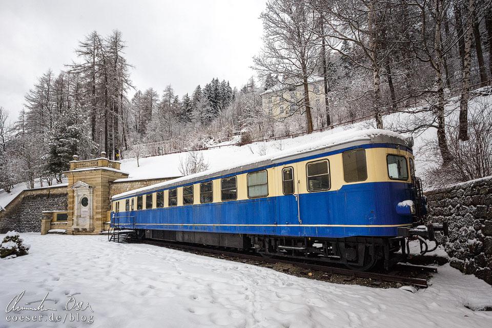 Denkmal von Carl von Ghega und ein alter blauer Triebwagen auf dem Bahnhof Semmering