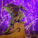 Abendliche Nahaufnahme eines der Drachen auf der Drachenbrücke mit einem beleuchteten Weihnachtsbaum im Hintergrund