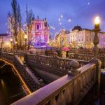 Die abendlich beleuchteten Drei Brücken mit der Mariä-Verkündigungs-Kirche im Hintergrund