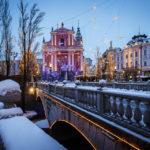 Die verschneiten Drei Brücken mit der Mariä-Verkündigungs-Kirche im Hintergrund