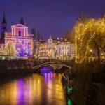 Die Mariä-Verkündigungs-Kirche, die Drei Brücken und der Fluss Ljubljanica mit prachtvoller Weihnachtsbeleuchtung