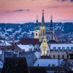 Aussicht vom Balkon des Feuerturms auf die Ursulinenkirche und die Dominikanerkirche von Sopron in der Abenddämmerung
