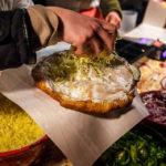 Neben Knoblauch, Rahm und Käse kann man auch noch Speck oder ungarische Salami auf den Langos hinzufügen