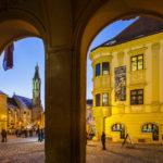 Blick durch die Arkaden des Rathauses auf die Ziegenkirche und das Storno-Haus