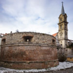 Eine Bastion der alten Stadtmauer und dahinter die Kirche St. Georg