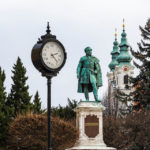 Denkmal des ersten Ehrenbürgers der Stadt Sopron, Graf István Széchenyi, mit den beiden Türmen der Dominikanerkirche und einer historischen Uhr