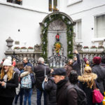 Touristen stehen rund um die Bronzefigur Manneken-Pis