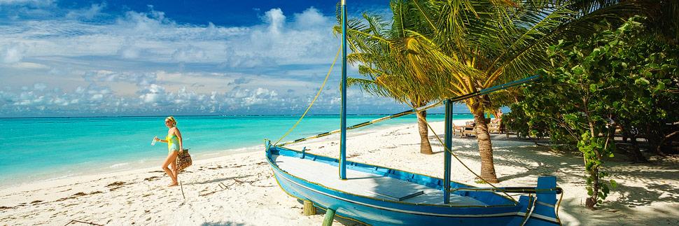 Frau zwischen Palmen am Strand von Meeru (Malediven)