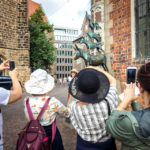 Touristen fotografieren die Bronzeskulptur der Bremer Stadtmusikanten