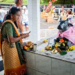 Eine Pilgerin legt Opfergaben vor die Statue der Heiligen Kuh am Grand Bassin