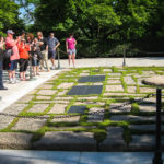 Besucher am Grab des US-Präsidenten John F. Kennedy, daneben die Ewige Flamme (Eternal Flame)