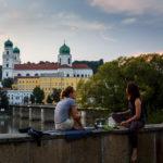 Zwei Mädchen vor dem Dom St. Stephan in Passau während eines Sonnenuntergangs