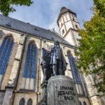 Außenansicht der Thomaskirche in Leipzig mit Statue von Johann Sebastian Bach