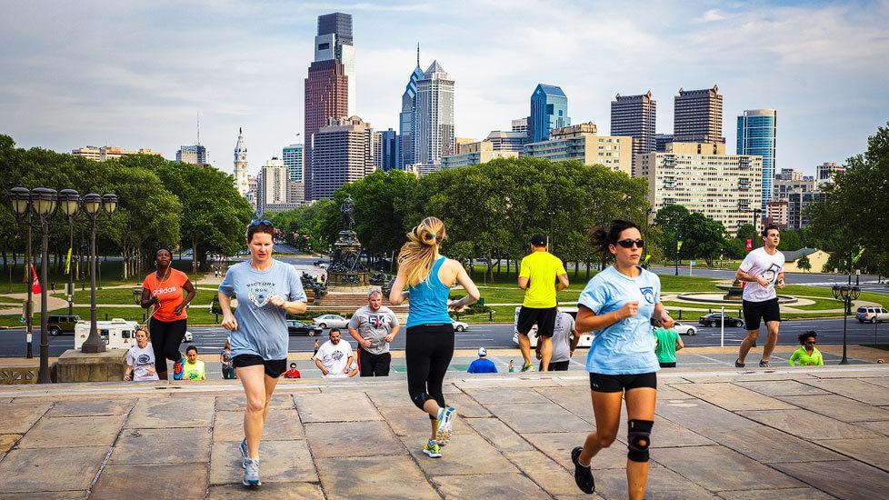 Läufer auf den Rocky Steps vor der Skyline von Philadelphia