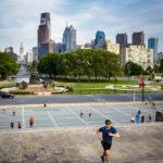 Läuferinnen und Läufer auf den Rocky Steps vor der Skyline von Philadelphia