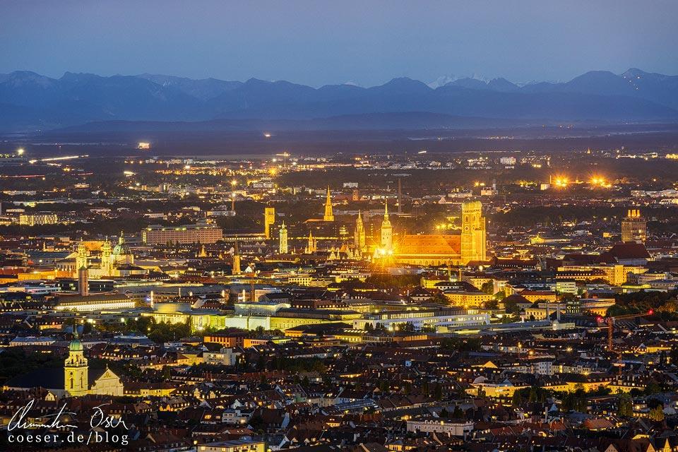 Münchner Innenstadt in der Abenddämmerung mit Gebirgslandschaft im Hintergrund