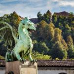 Drache auf der Drachenbrücke, im Hintergrund die Burg von Ljubljana