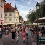 Zahlreiche Menschen auf der Uferpromenade Petkovškovo nabrežje in Ljubljana