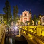 Nachtaufnahme der Drei Brücken und der Mariä-Verkündigungs-Kirche auf dem Prešeren-Platz in Ljubljana