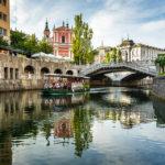 Blick auf den Prešeren-Platz mit der Mariä-Verkündigungs-Kirche und den Drei Brücken während einer Bootsfahrt auf der Ljubljanica in Ljubljana