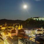 Blick von der Terrasse des Wolkenkratzers Nebotičnik auf die beleuchtete Innenstadt und Burg von Ljubljana