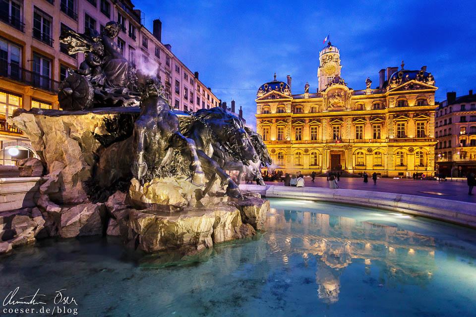 Abendaufnahme des Hôtel de ville und Fontaine de Bartholdi am Place des Terreaux in Lyon