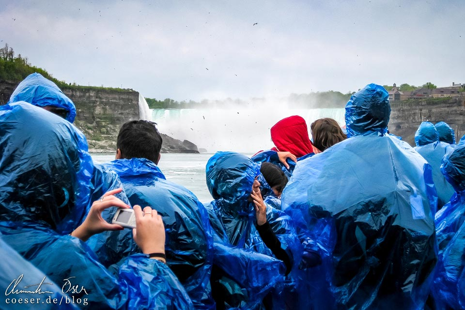 Besucher mit Regencapes auf der Maid of the Mist vor den Niagarafällen