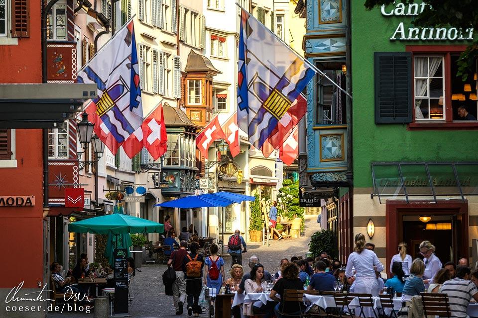 Augustinergasse in Zürich mit stimmungsvollen Schweizer Fahnen und interessanten Erkern