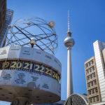 Die Urania-Weltzeituhr auf dem Alexanderplatz mit Blick auf den Fernsehturm in Berlin
