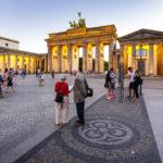 Touristen vor dem Brandenburger Tor kurz vor Sonnenuntergang in Berlin