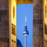 Blick durch das Brandenburger Tor auf den Fernsehturm kurz nach Sonnenuntergang in Berlin