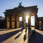 Zwei Radfahrer vor dem Brandenburger Tor kurz nach Sonnenaufgang in Berlin