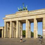 Ein Jogger vor dem Brandenburger Tor kurz nach Sonnenaufgang in Berlin