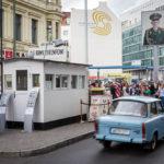 Ein Trabi überquert den früheren Grenzübergang Checkpoint Charlie in Berlin