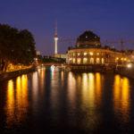 Nachtaufnahme des beleuchteten Bode-Museums und des Fernsehturms in Berlin