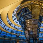Besucher in der beleuchteten Kuppel im Reichstagsgebäude in Berlin