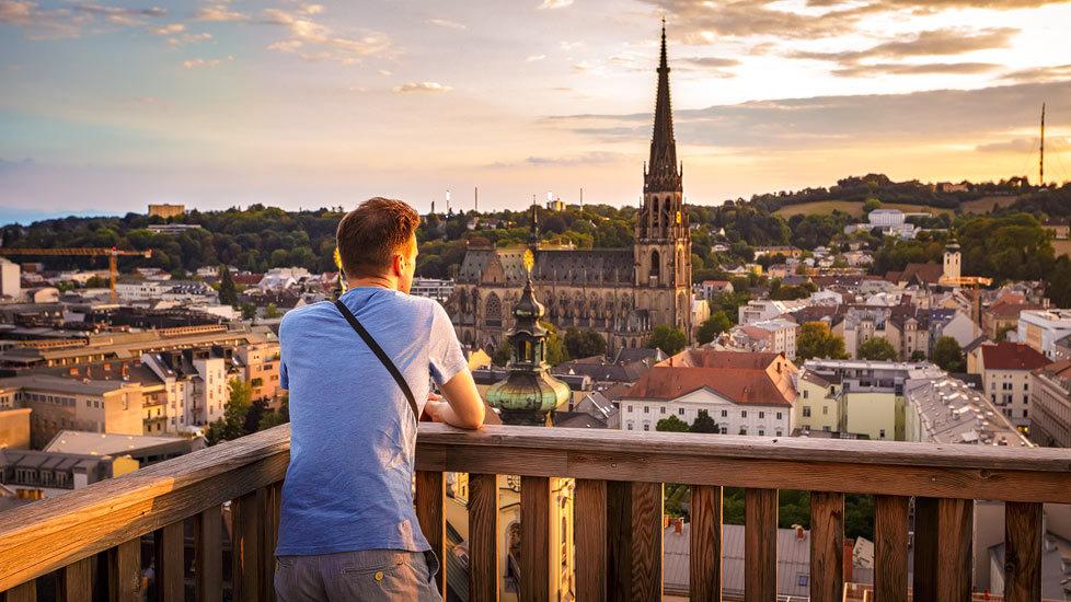 Mann blickt während eines Sonnenuntergangs auf Linz