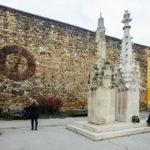Links vom Eingang der Kathedrale von Zagreb erinnert eine alte Kirchturmuhr an das Erdbeben von 1880, daneben sieht man eine verfallene und eine restaurierte Säule
