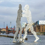 """Das Kunstwerk """"Molecule Man"""", dahinter die Oberbaumbrücke in Berlin"""