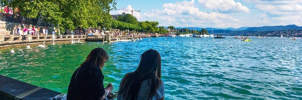 Zwei Mädchen sitzen am Zürisee in Zürich