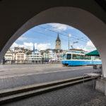 Blick durch einen Torbogen auf die Pfarrkirche St. Peter und eine Straßenbahn in Zürich