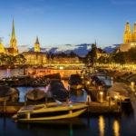 Klassischer Blick auf Zürich bei Nacht mit Fraumünster, Pfarrkirche St. Peter und Grossmünster