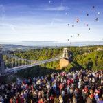 Zuschauer und Heißluftballons hinter der Clifton Suspension Bridge während der Bristol Balloon Fiesta
