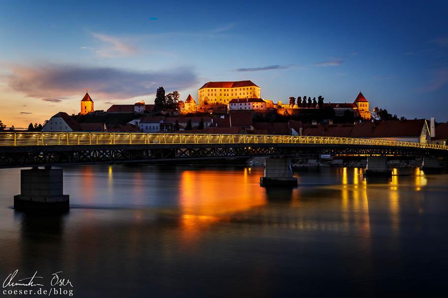 Fußgängerbrücke und beleuchtetes Schloss von Ptuj