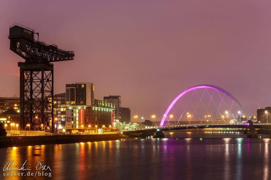 Nachtansicht der Clyde Waterfront von Glasgow mit dem Finnieston Crane und der Brücke The Clyde Arc
