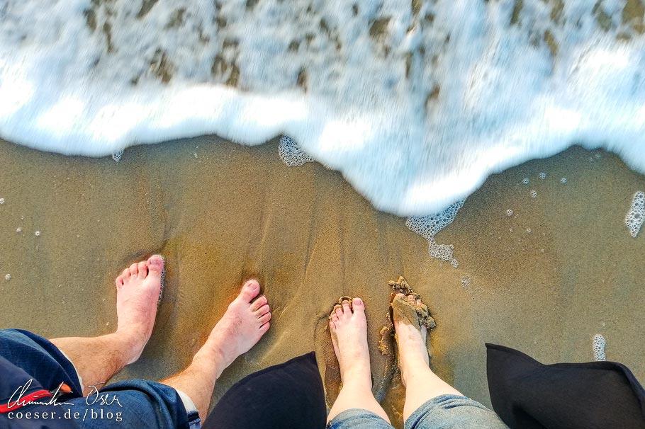 Ein Liebespaar steht mit den Füßen im Meer