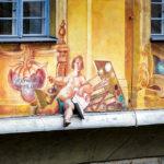 Ein plastisches Bein schaut aus der Freskenfassade am Alten Rathaus in Bamberg heraus