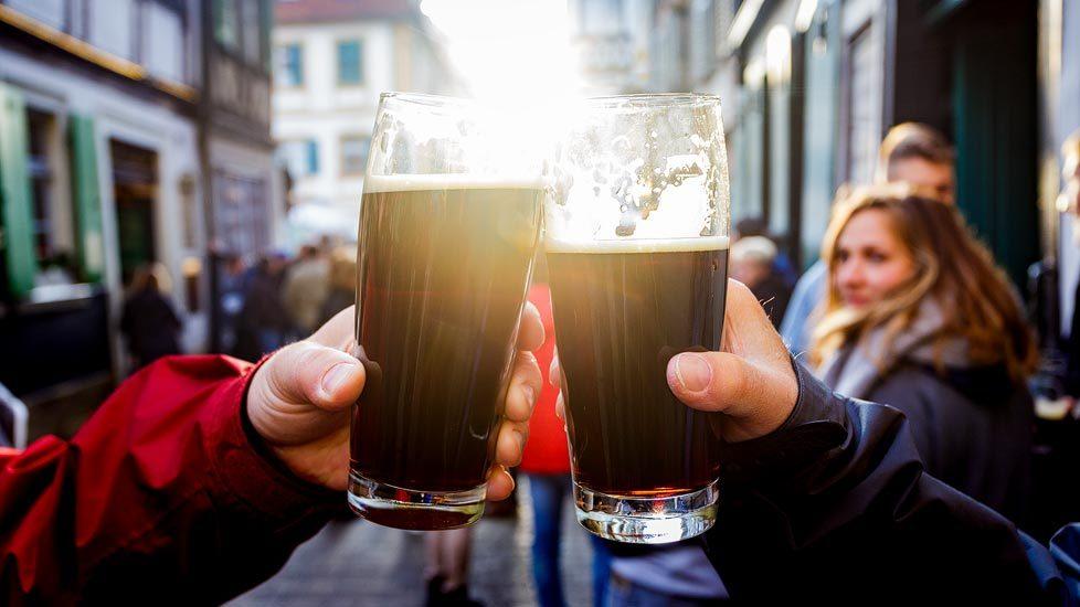 Zwei Personen stoßen mit Rauchbier der Brauerei Schlenkerla in Bamberg an