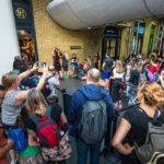 Harry-Potter-Fans stehen rund um Gleis 9 3/4 im Bahnhof King's Cross