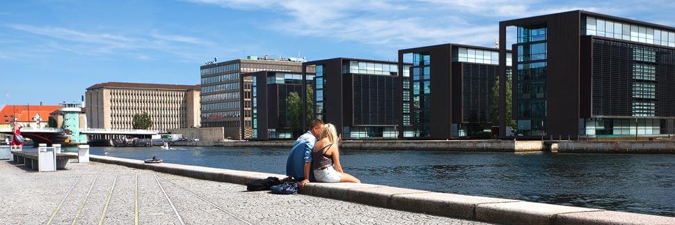 Ein Paar sitzt am Wasser mit Blick auf das Steuerministerium in Kopenhagen
